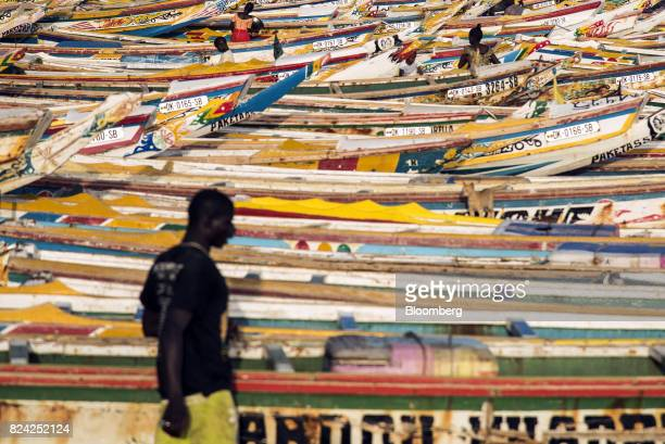 A man walks by hundreds of painted fishing boats at the Soumbedioune fish market in Dakar Senegal on Friday July 28 2017 Senegalese voters will elect...