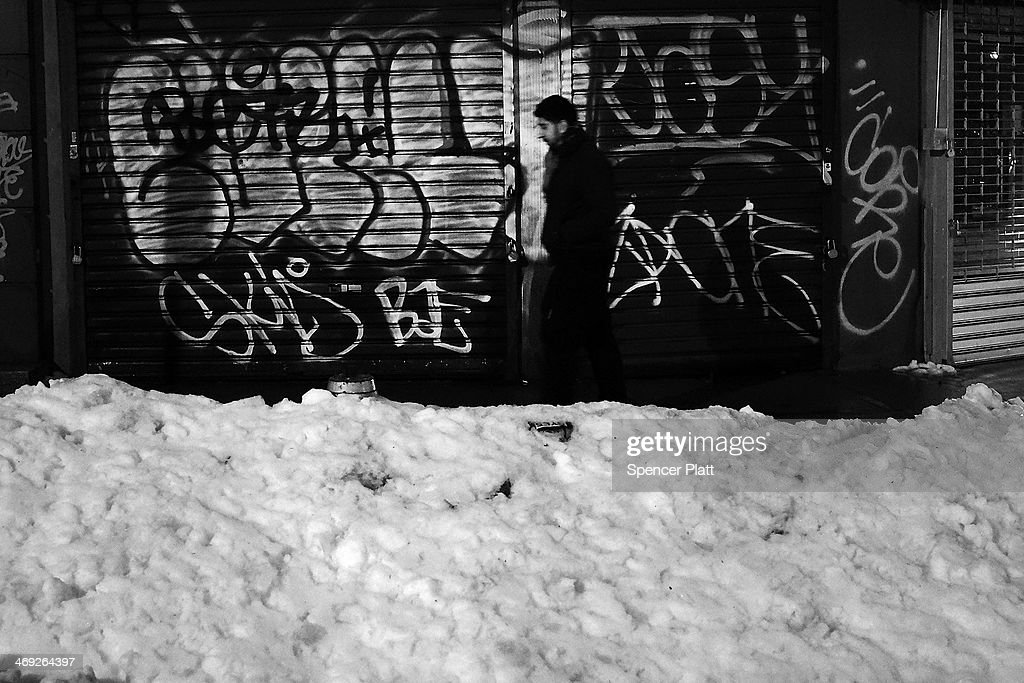 A man walks by mounds of snow on February 13, 2014 in New York City. In what is turning out to be one of the snowiest winter's in recent memory for New York City and much of the East Coast, Thursday's weather is expected to bring a wintery mix of sleet and snow with a total accumulation of over 8 inches of snow before ending early Friday morning.