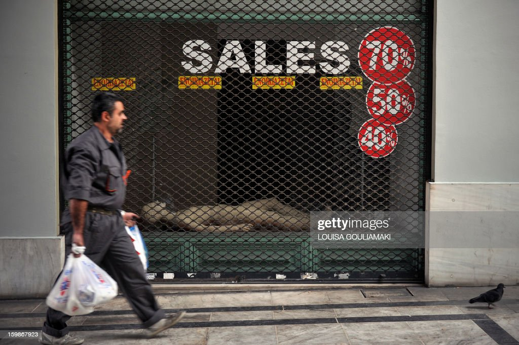 A man walks by one of hundreds shut down stores in the center of Athens on January 22, 2013. Entering a sixth year straight of recession, the heavily indebted country is relying on EU-IMF bailout packages. Since 2010, the EU and International Monetary Fund (IMF) have committed 240 billion euros (320 billion US dollars) in rescue loans to Greece, while last week the IMF unblocked a frozen tranche of 3.2 billion euros from its pending aid package. GOULIAMAKI