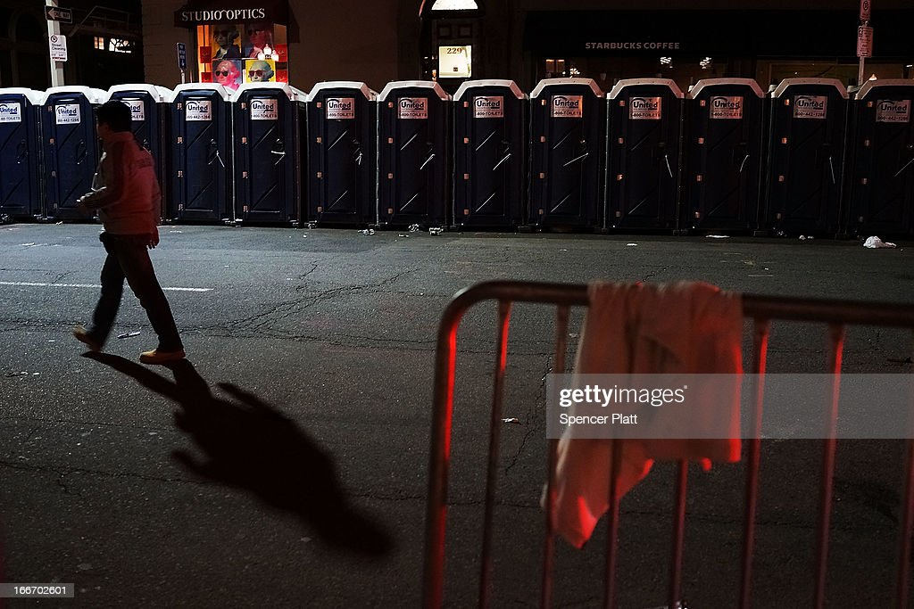 A man walks by portable toilets near the scene of a twin bombing at the Boston Marathon, on April 16, 2013 in Boston, Massachusetts. Three people are confirmed dead and at least 141 injured after the explosions went off near the finish line of the marathon yesterday. The bombings at the 116-year-old Boston race, resulted in heightened security across the nation with cancellations of many professional sporting events as authorities search for a motive to the violence.