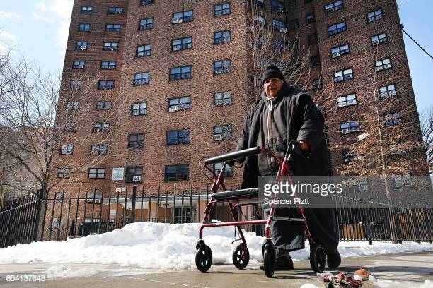A man walks by the Farragut Houses a public housing project in Brooklyn on March 16 2017 in New York CityThe budget blueprint President Donald Trump...