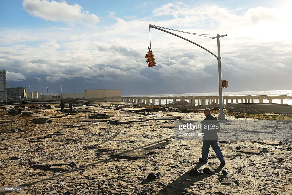 A man walks by the remains of part of the historic Rockaway boardwalk after large parts of it were washed away during Hurricane Sandy on October 31, 2012 in the Queens borough of New York City. With the death toll currently at 55 and millions of homes and businesses without power, the US east coast is attempting to recover from the affects of floods, fires and power outages brought on by Hurricane Sandy. JFK airport in New York and Newark airport in New Jersey expect to resume flights on Wednesday morning and the New York Stock Exchange commenced trading after being closed for two days.