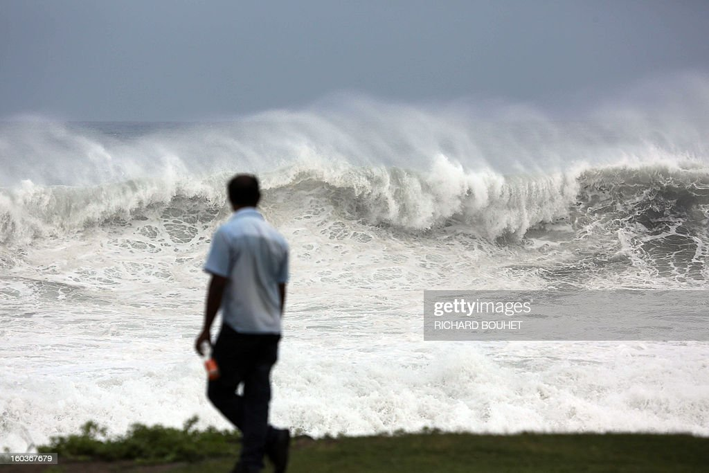 A man walks by the sea on the North coast of French Indian Ocean island of La Reunion on January 30, 2013 near Saint-Denis, as high waves hit the coastline. The cyclone Felleng was announced at 735 Km north of the island and progresses at the speed of 17 Km per hour. Felleng should approach the coast of the island from 300 km on February 1st.