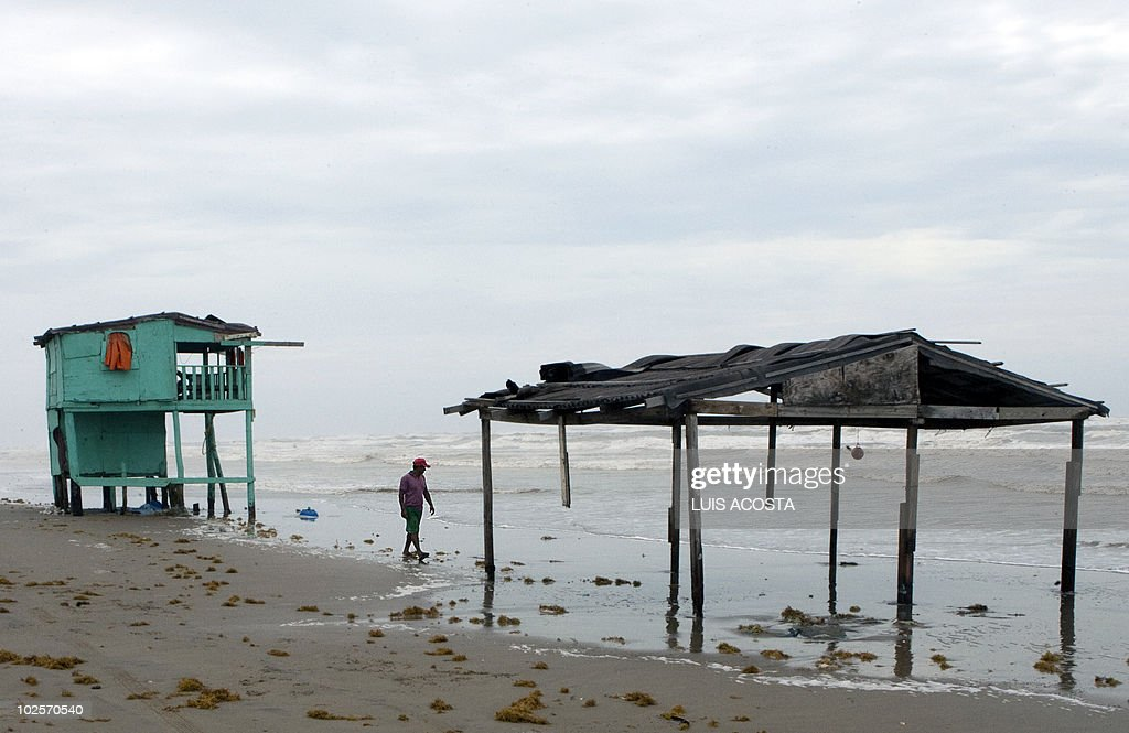 A man walks by the shore after the passage of Hurricane Alex in Bagdad Beach, in Matamoros, Tamaulipas State, on July 1, 2010. Alex, the first hurricane of the Atlantic season, weakened across northeast Mexico as it neared high mountains on Thursday, after disrupting oil clean-up operations in the Gulf of Mexico. Alex was downgraded to a tropical storm after roaring ashore late Wednesday as a Category Two hurricane slightly south of the eastern US-Mexico border. AFP PHOTO/Luis Acosta