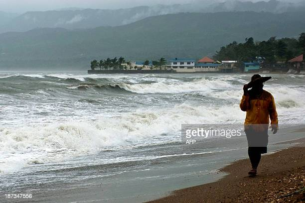 A man walks by the shoreline as Super Typhoon Haiyan smashes into coastal communities on the central island of Cebu on November 8 2013 One of the...