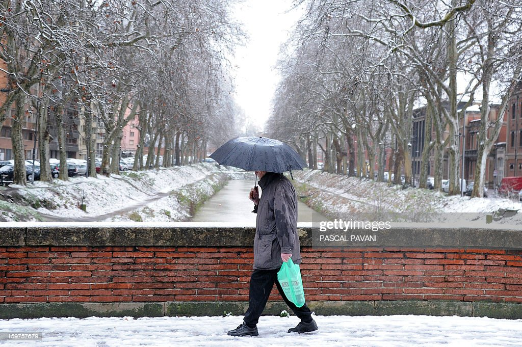 A man walks by the snow covered banks of the Canal de Brienne, on January 20, 2013 in Toulouse southern France, after heavy snow falls.