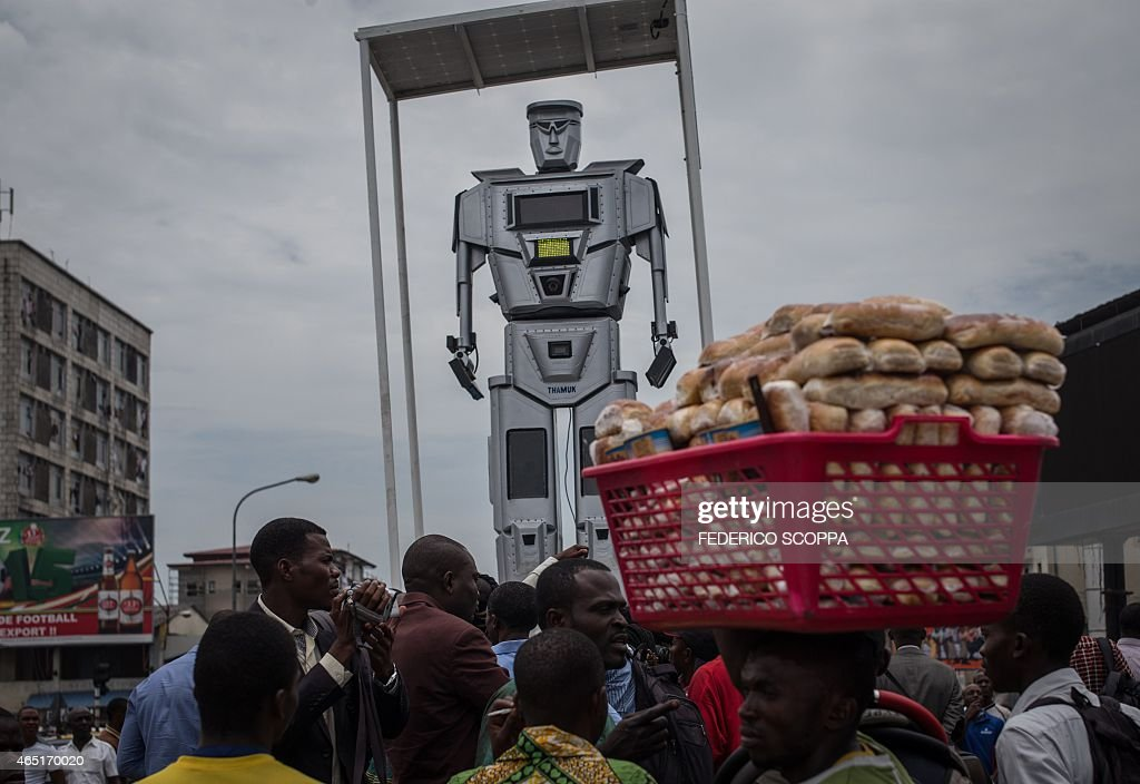 A man walks by with a basket of bread during the official presentation ceremony of three new humanlike robots that were recently installed in...