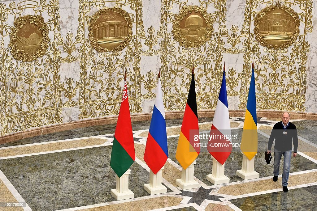 A man walks close to the flags of France Russia Germany Ukraine and Belarus at the presidential residence in Minsk on February 11 2015 The leaders of...