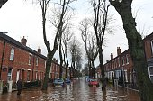 A man walks down a flooded street in Carlisle on December 6 2015 One man was killed yesterday as Storm Desmond whipped across Britain bringing heavy...