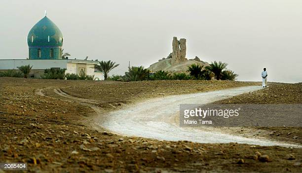A man walks down a road in the shadow of a Mesopotamian ziggurat and a shrine to the prophet Abraham June 8 2003 in Borsippa Iraq The ziggurat a...