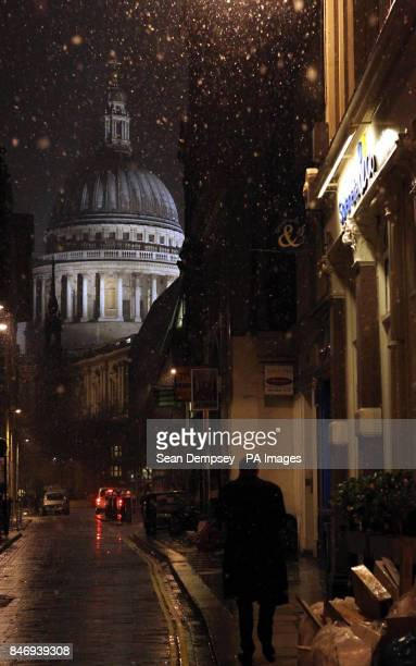 A man walks down a road in the snow towards St Paul's Cathedral in London as up to four inches of snow is expected to fall in parts of England and...