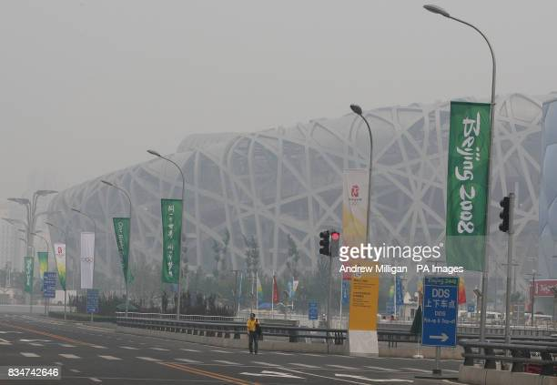 A man walks down a road past the National Stadium in Beijing China