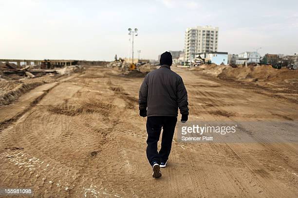 A man walks down a sand road in the heavily damaged Rockaway neighborhood where a large section of the iconic boardwalk was washed away on November...