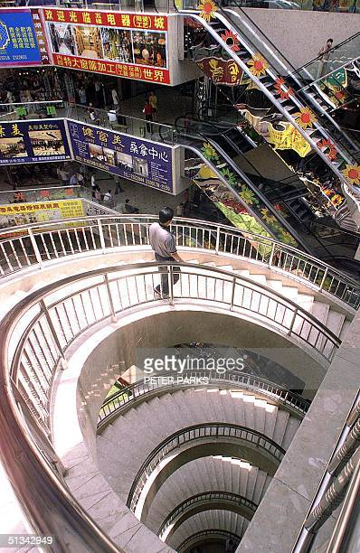 A man walks down a staircase in a shopping mall in Shenzhen 13 August 2001 Chinese consumer spending rose 98 percent in July from a year earlier...