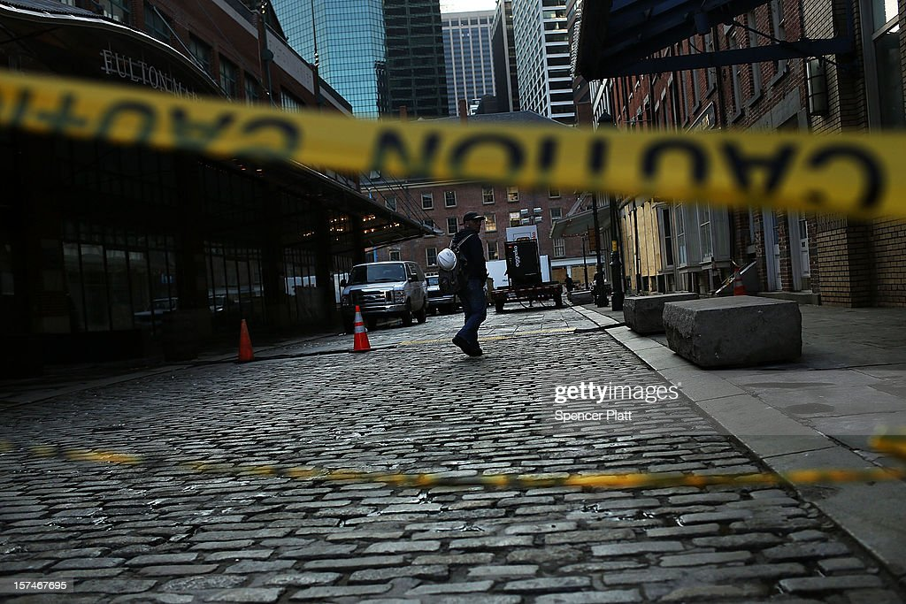 A man walks down a street affected by Superstorm Sandy in the heavily damaged South Street Seaport on December 3, 2012 in New York City. South street Seaport, an area popular with tourists which was about to go through a major redevelopment, suffered severe damage from Hurricane Sandy. Most of the buildings and businesses, including the South Street Seaport Museum, suffered severe flooding and remained closed. According to a new Siena Research Institute poll, most New Yorkers overwhelmingly agree that climate change was behind Hurricane Sandy.