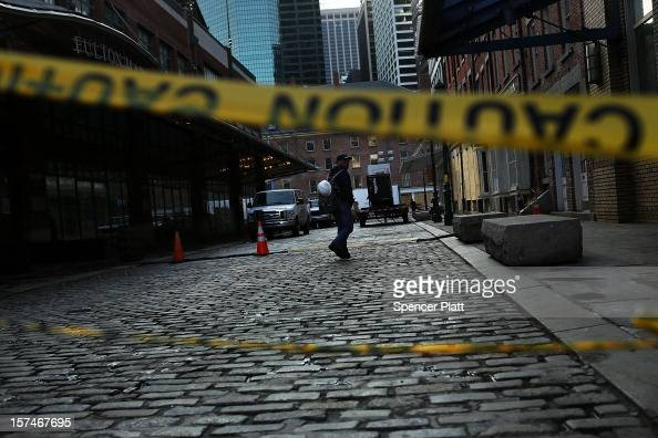 A man walks down a street affected by Superstorm Sandy in the heavily damaged South Street Seaport on December 3 2012 in New York City South street...