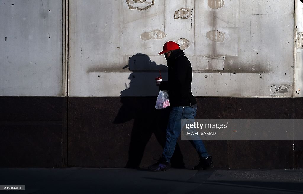 A man walks down a street early cold morning in downtown Manhattan, New York, on February 14, 2016. / AFP / Jewel Samad