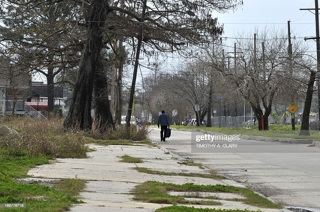 A man walks down a street in the Lower Ninth Ward of New Orleans on February 5, 2013. The Ninth Ward suffered the worst damage from Hurricane Katrina that occured in 2005 after multiple breaches in the levees of at least four canals. As of March 2009, hundreds of houses have been rebuilt, and dozens of new homes have been constructed.