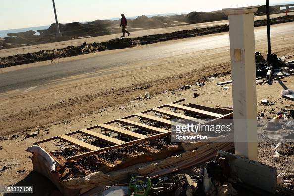 A man walks down a street littered with debris near the beach in Rockaway on December 13 2012 in New York City Much of the Rockaway neighborhood is...