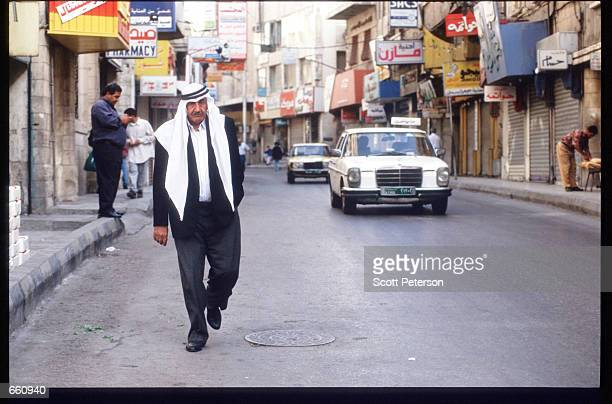 A man walks down a street May 17 1998 in Amman Jordan Still a teenager when crowned in 1952 King Hussein has led the young Arab nation through brief...