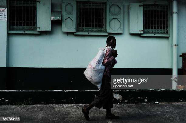 A man walks down a street on December 10 2017 in St John's Antiqua While it's sister island Barbuda was nearly destroyed by Hurricane Irma Antiqua...