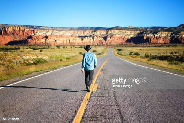Mann geht in Mitte des schönen leeren Western Highway