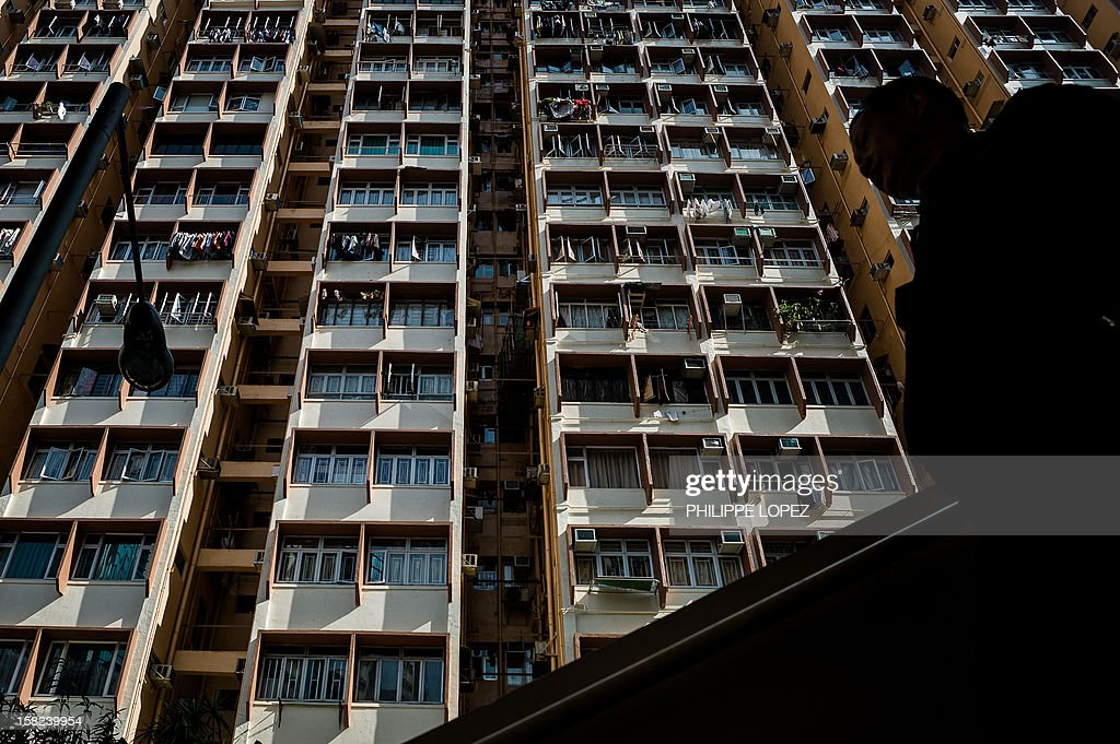 A man (R) walks down stairs in front of a high rise residential building in Hong Kong on December 12, 2012. The International Monetary Fund warned that Hong Kong could see an abrupt fall in property prices after years of dramatic increases in one of the world's most expensive housing markets. AFP PHOTO / Philippe Lopez