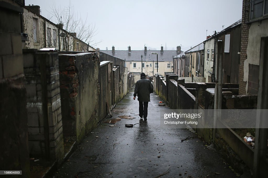 A man walks down the alleyway at the back of former council houses a street in the Lancashire town of Accrington as they wait to be modernised by private developers on January 3, 2013 in Accrington, England. There are estimated to be 850,000 empty homes in the United Kingdom even though local councils still have long waiting lists for housing. The terraced houses were due to be rejuvenated by Accrington council but the project was put on hold when the government cut a housing regeneration project.