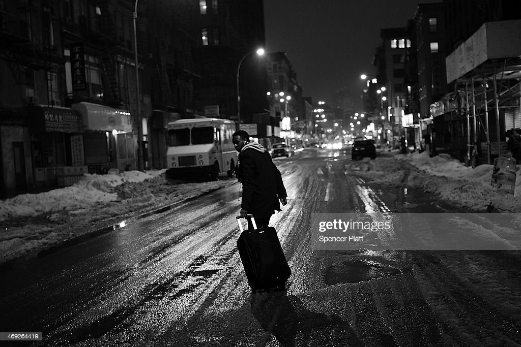 A man walks down the middle of a street in the snow and rain on February 13, 2014 in New York City. In what is turning out to be one of the snowiest winter's in recent memory for New York City and much of the East Coast, Thursday's weather is expected to bring a wintery mix of sleet and snow with a total accumulation of over 8 inches of snow before ending early Friday morning.