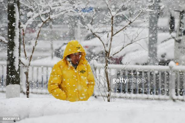 A man walks during snowfall in Yantai in China's eastern Shandong province on December 12 2017 A blue alert for a snowstorm and a yellow alert for...