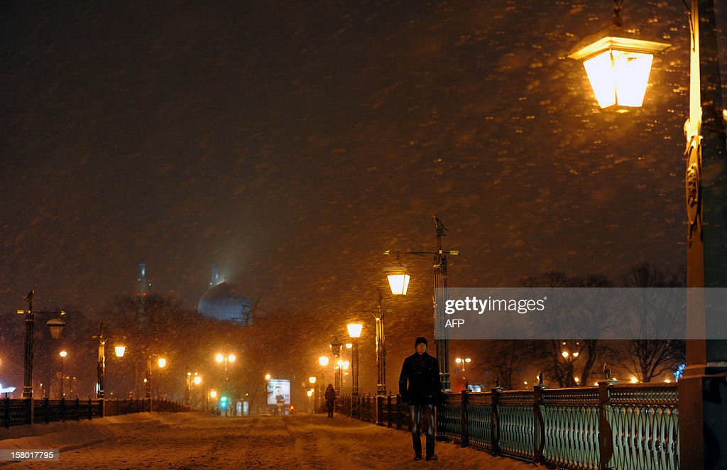 A man walks during snowfall near the Saint-Peter and Paul fortress in central St.Petersburg, late on November 8, 2012. Snow fell yesterday across the Russia's second city, while temperatures dropped today to -6 C (21 F). AFP PHOTO / OLGA MALTSEVA