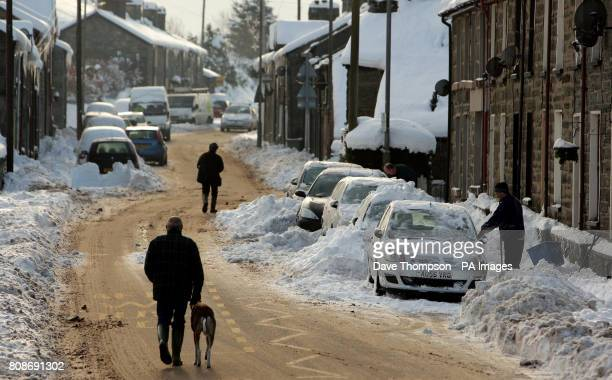 A man walks his dog down the middle of the road in Blaenau Ffestiniog North Wales after temperatures plunged overnight