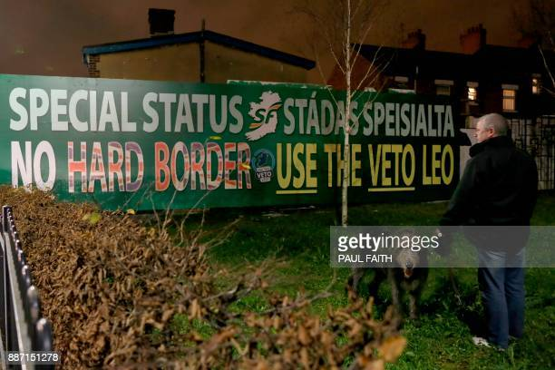 A man walks his dog in front of a new antiBrexit mural erected by Republican party Sinn Fein in west Belfast on December 6 2017 to call for a special...