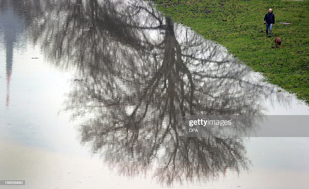 A man walks his dog on the border of the river Rhine flooding its banks on December 19, 2012 in Duesseldorf, western Germany. Due to melting snow and rainfalls, cities situated on the banks of the Rhine expect more flood waters.