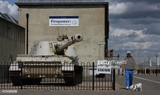 A man walks his dog past a 2S3 M1973 Akatsiya 152mm selfpropelled gun howitzer stands outside the Greenwich Heritage Centre set up as a polling...