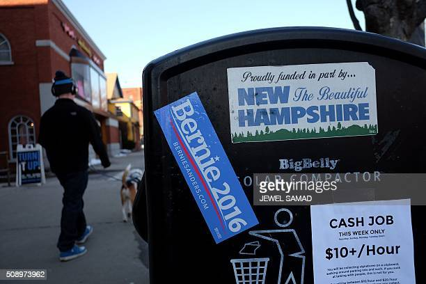 A man walks his dog past a trash bin where a campaign sticker for US Democratic presidential candidate Bernie Sanders is pasted in Keene New...
