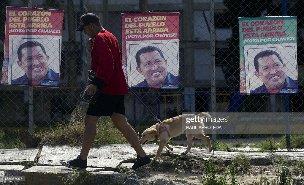A man walks his dog past posters of Venezuelan President Hugo Chavez, in Caracas on January 4, 2013. Hugo Chavez's top aides have gone on the offensive, accusing the opposition and media of waging a 'psychological war,' as Venezuela's cancer-stricken president battles a serious lung infection. The closing of ranks followed a high-level gathering of top Venezuelan officials in Havana with Chavez, amid growing demands to know whether he will be fit on January 10 to take the oath of office for another six-year-term. AFP PHOTO/Raul ARBOLEDA