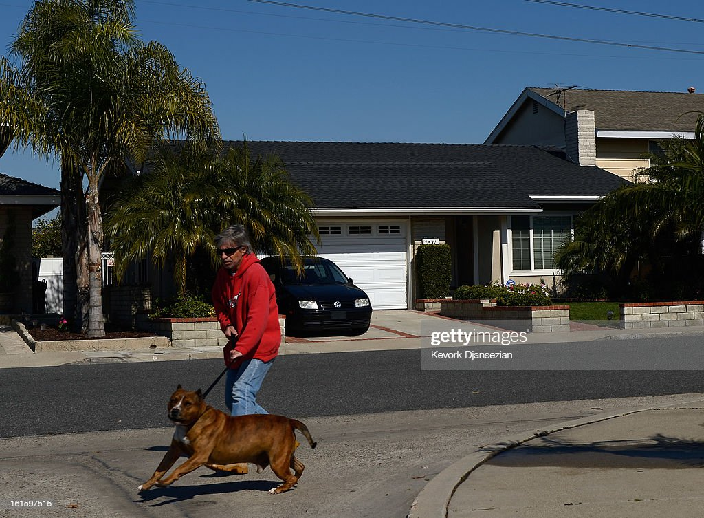 A man walks his dog past the house of Christopher Dorner's mother as the manhunt continues for the murder suspect on February 12, 2013 in La Palma, California. Dorner, a former Los Angeles Police Department officer and Navy Reserve veteran, is wanted in connection with the deaths of an Irvine couple and a Riverside police officer. LAPD removed evidence during the search of the house owned 62-year-old Nancy Dormer. The manhunt for Christopher Dorner has gone international as police raided a Mexican hotel overnight in Tijuana, Mexico.