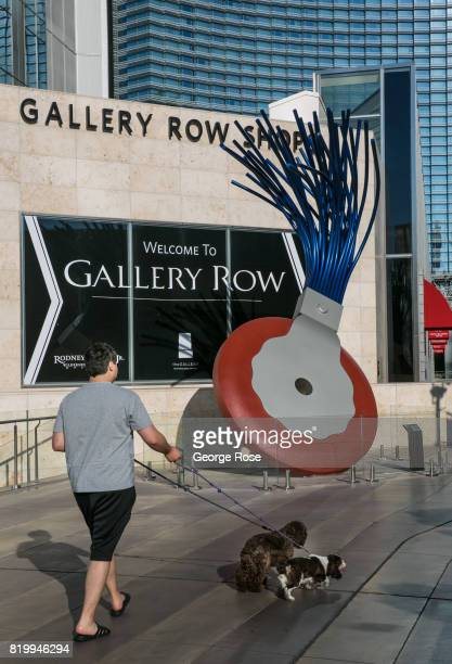 A man walks his dogs past a Claes Oldenburg 'Typewriter Eraser' sculpture at the CityCenter Gallery Row near the Aria Hotel Casino on July 14 2017 in...