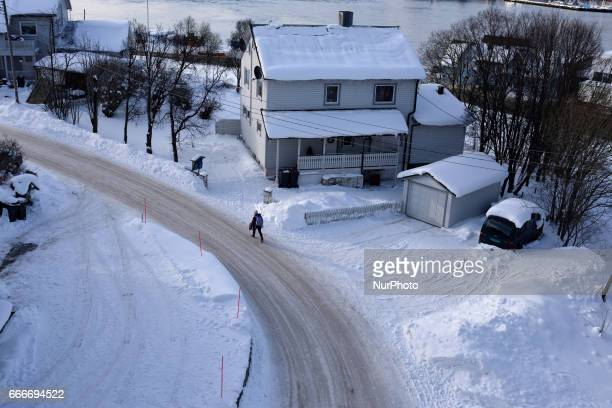A man walks in a a street in the snowcovered city of Tromso Northern Norway on March 08 2017 Troms is located 350 kilometres north of the Arctic...