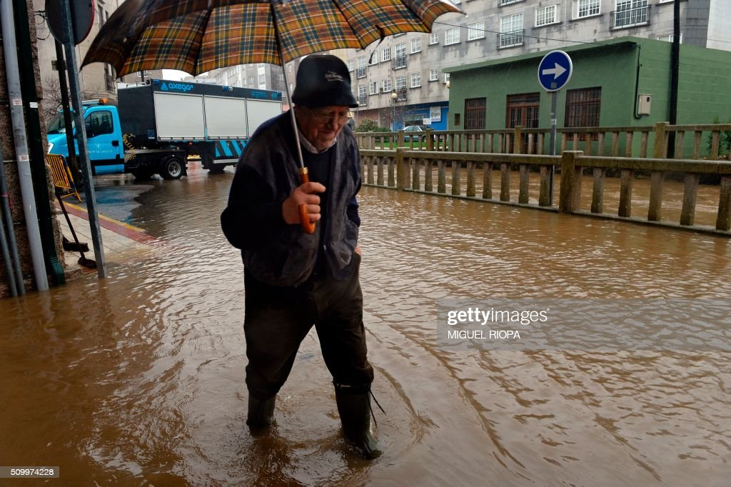 A man walks in a flooded area next to the river Tea in Ponteareas, northwestern Spain, on February 13, 2016. / AFP / AFP or licensors / MIGUEL RIOPA