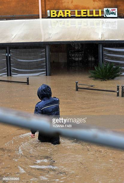A man walks in a flooded streets in 'Prima Porta' in the outskirts of Rome after torrential rains hit the region overnight on January 31 2014 AFP...