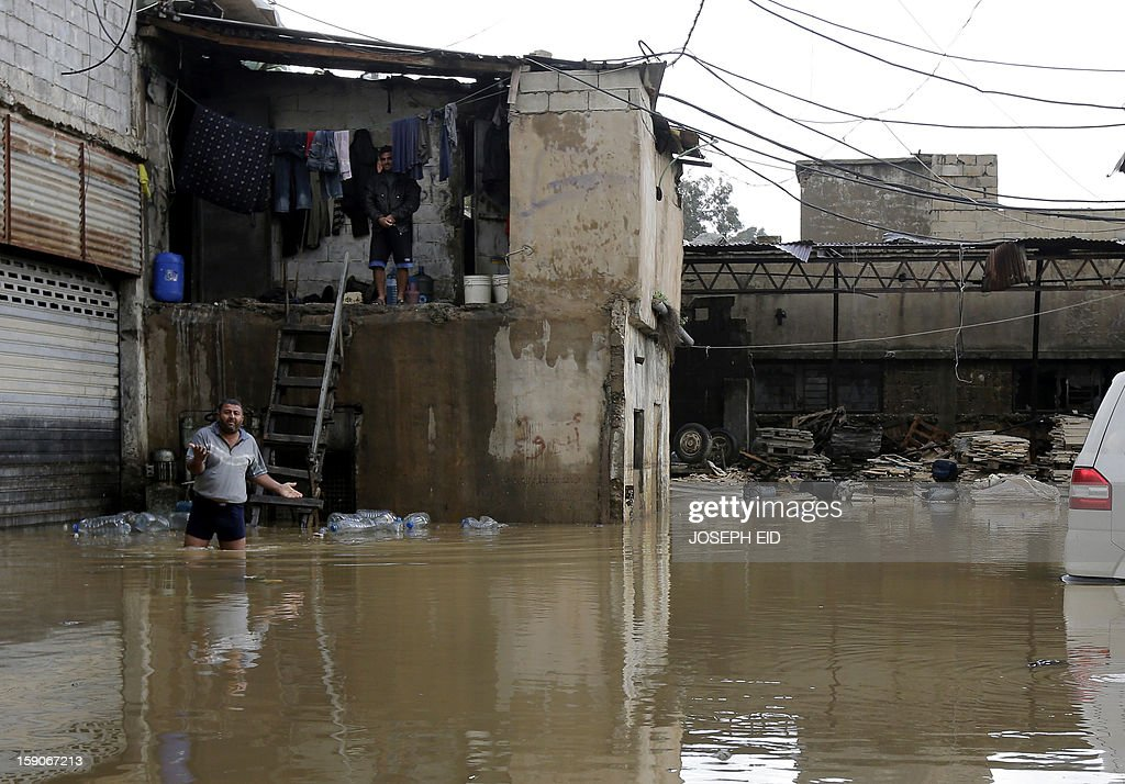 A man walks in a flooded yard as he walks out of his squat in the Lebanese capital Beirut, on January 7, 2013. Stormy weather, including high winds and heavy rainfall, lashed the eastern Mediterranean coast, downing power lines and trees and causing several injuries in a number of countries.