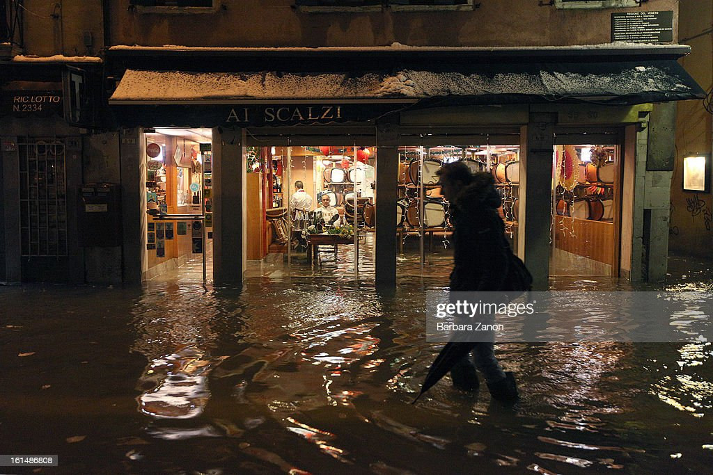 A man walks in a street during a heavy snow and high tide on February 11, 2013 in Venice, Italy. Heavy snow, high water, rain and wind hit the city today and sea level rose to 145cm.