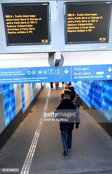 A man walks in a tunnel under two monitor screens alerting of the interuption of the railway trafic due to a catenary pullout on December 7 2016 at...