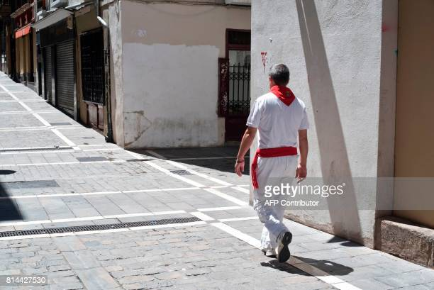 A man walks in an empty street during the last day of the San Fermin festival in Pamplona northern Spain on July 14 2017 The festival is a symbol of...