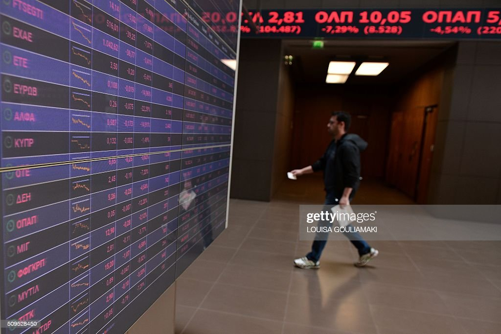 A man walks in Athens stock exchange on February 11, 2016. Greek stocks shed over 6 percent in value amid a broader European slide fueled by oil price worries and global economy fears. The Athens stock exchange fell to 421.25 points at around midday, with the economic climate in Greece also burdened by concerns over the country's tortuous reform talks with its EU-IMF creditors. / AFP / LOUISA GOULIAMAKI