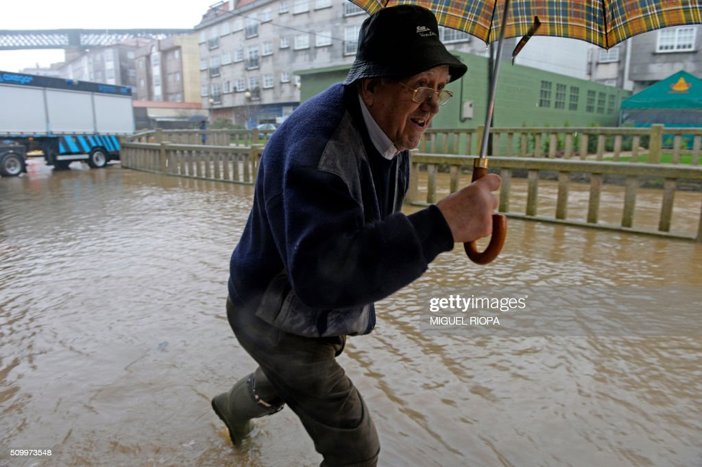 A man walks in flooded area next to the river Tea in Ponteareas, northwestern Spain, on February 13, 2016. / AFP / AFP or licensors / MIGUEL RIOPA