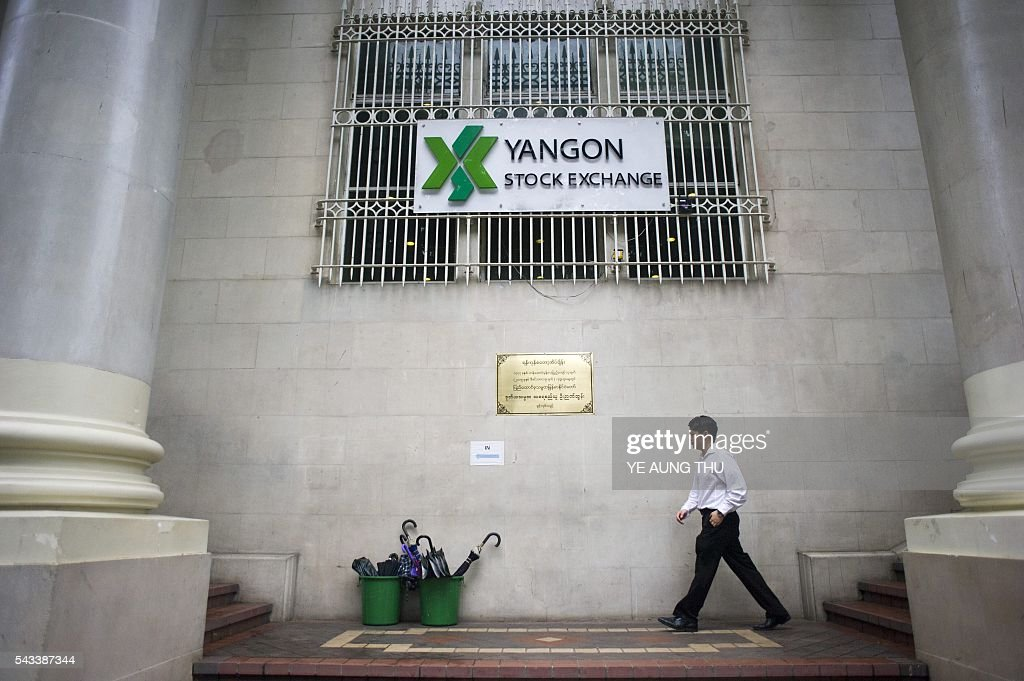 A man walks in front if the Yangon Stock Exchange building in Yangon on June 28, 2016. / AFP / YE