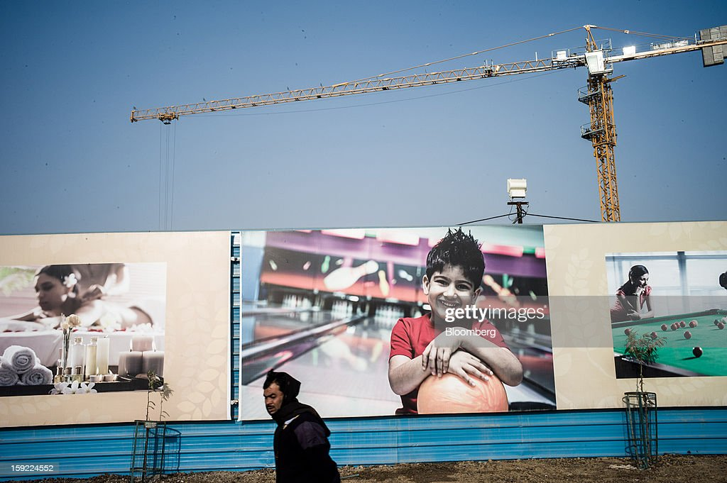 A man walks in front of a fence surrounding a construction site in Noida, Uttar Pradesh, India, on Wednesday, Jan. 9, 2013. India's Finance Ministry predicts GDP growth of as little as 5.7 percent in the year to March 31, the least in a decade. Photographer: Sanjit Das/Bloomberg via Getty Images